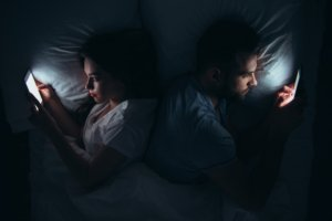 Image: couple lying back-to-back in bed, each glued to their smartphone