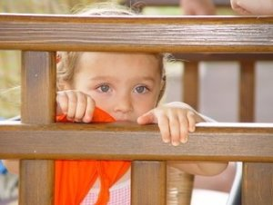 young boy in a the bed's railings