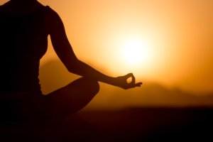 Image: Silhouette of a woman meditating turned towards the sunset