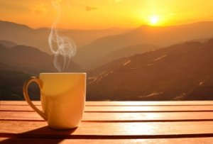 Image: Sunrise in the mountains. Steam wafts off a cup of coffee.