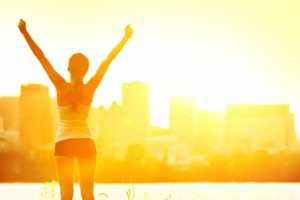 Image: girl salutes the sunrise, energized from her morning run