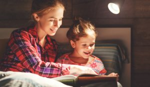 Image: mother reads to daughter before bed