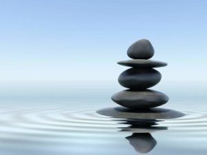 Image: five smooth pebbles stacked above still water