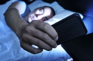 Image: man looking at his phone in bed