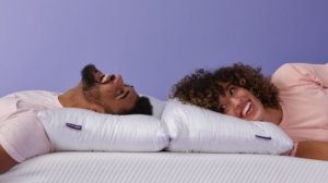 A man and woman lying down on purple plush pillows