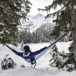Image: A hiker sits in a Rallt camping hammock, overlooking a snow-covered clearing with pine trees and mountains in the background