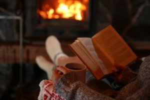 Image: woman reads beside a roaring fireplace