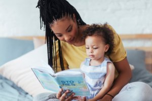 Image: mother reads to her daughter in bed