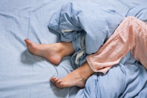 Image: legs of a woman restless in bed