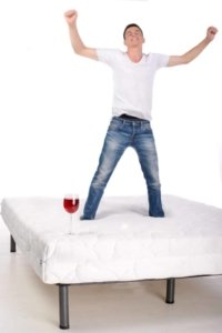 Man jumping on bed with undisturbed wine glass