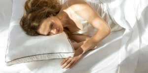 A woman resting on the Saatva Dreams Pillow