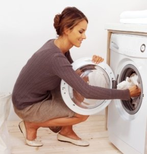 Woman puts laundry into washer