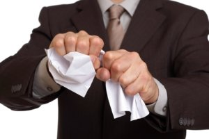Man in suit tears up a paper