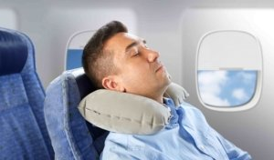 Image: man with neck pillow asleep on plane
