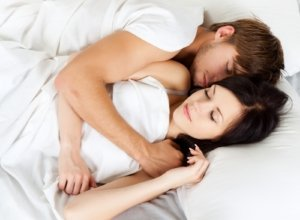 Image: sleeping couple cuddles in bed