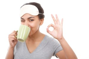Image: girl with a sleep mask and cup of tea looks incredibly ready to go to sleep