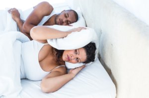 Image: woman covering ears to block out man's snoring