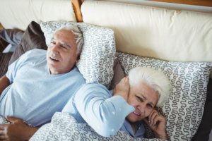 Image: man snoring while woman covers ears