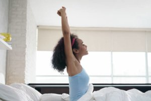 Image: woman stretches as she wakes up, ready to take on the day