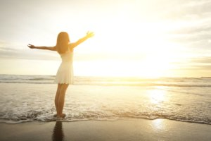 Image: woman stands on seashore, arms outstretched to embrace the morning