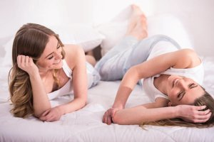 Image: two girls in their pjs lying on the bed, talking