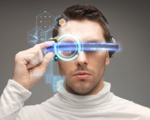 Image: A man in a white turtleneck taps a glowing, futuristic-looking visor around his eyes.