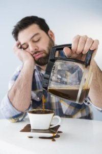 a guy pouring coffee while asleep