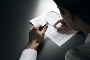 Image: Man uses a magnifying glass to read the fine print on a contract