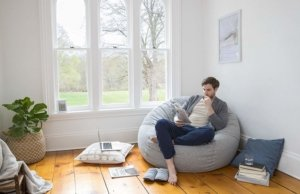 Image: man relaxing in his living room on a Tuft & Needle Pouch