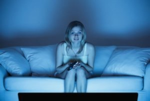 Image: woman watches tv at night