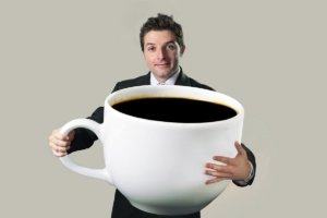 Image: businessman holding full coffee mug almost the size of himself