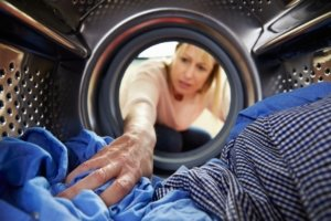 A lady washing clothes in the machine