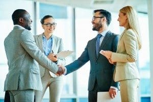 Two successful businessmen handshaking with female colleagues near by