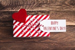 Valentines stripped red gift with red felt heart and greeting label on wooden background