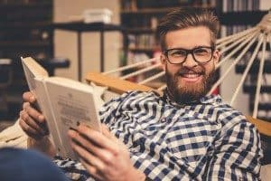 Handsome bearded young man is reading a book, looking at camera and smiling while lying in the hammock in modern library
