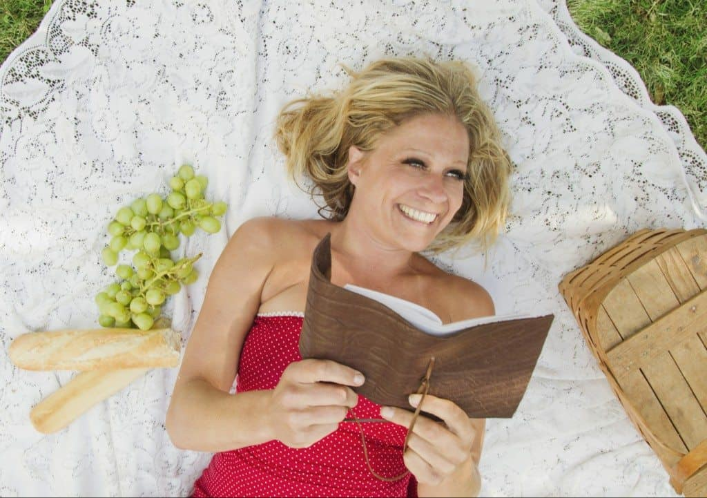 Woman reading book on picnic blanket