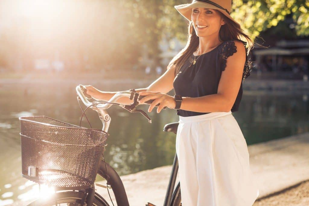 Outdoor shot of a pretty young woman with a bicycle in park during summer. Female with a cycle looking away smiling on a bright sunny day.