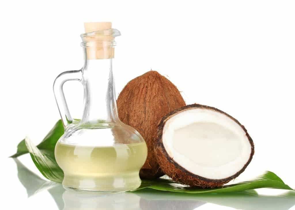 decanter with coconut oil and coconuts isolated on whitecoconut oil in bottles with coconuts on white backgroundcoconut oil in bottles with coconuts on green background