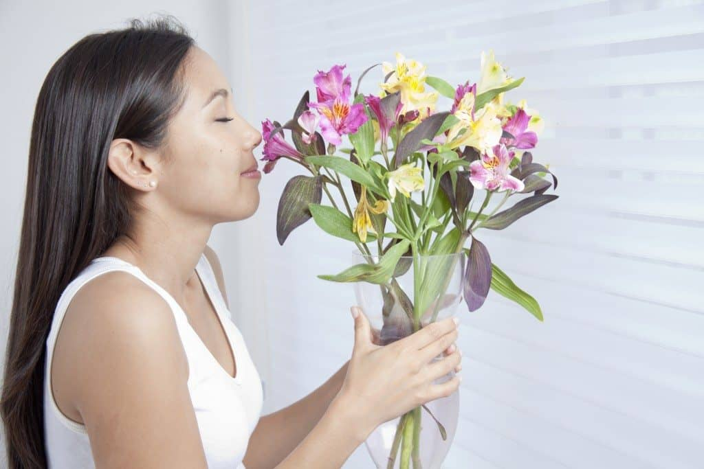 Young women sniff flowers