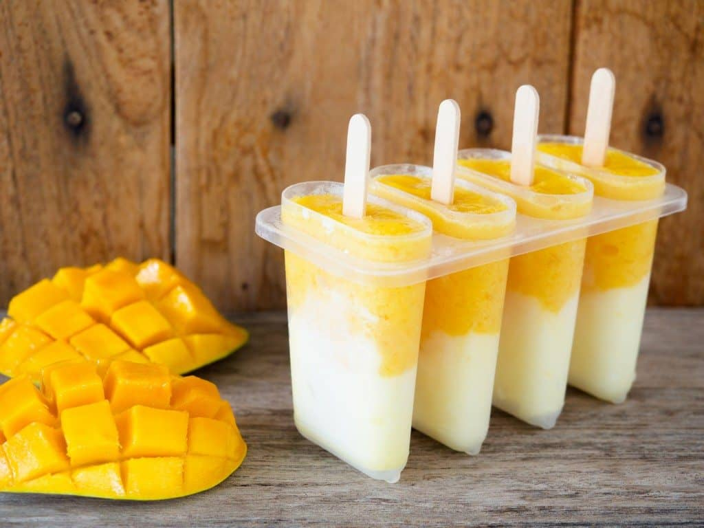 Homemade mango and yogurt popsicle for summer ice cream dessert concept.