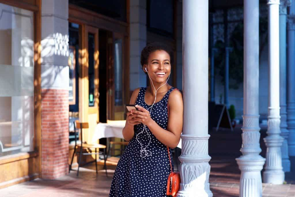 Portrait of smiling young woman standing outside with earphones and mobile phone