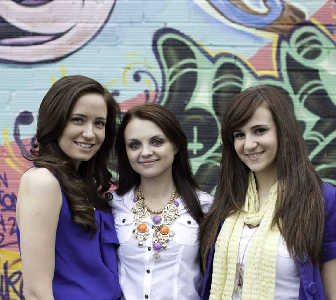"""""""Three young girls standing outdoors, smiling."""""""