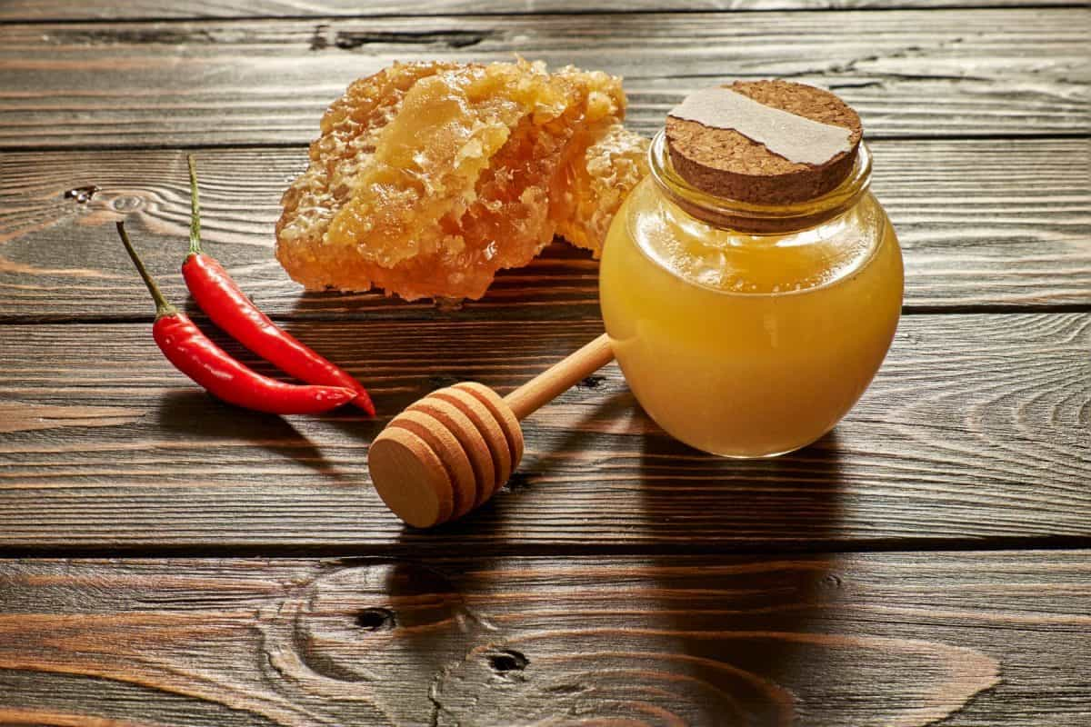 Honey and honeycomb with chili pepper and stick on wooden background