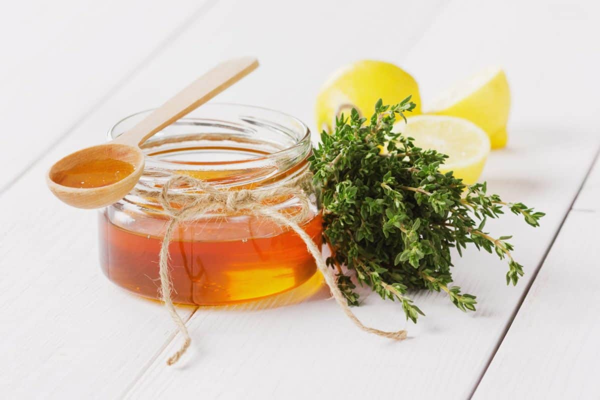 Honey in a wooden spoon and jar on a white background