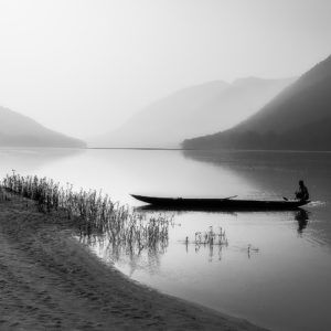 Black and white photography artwork of boat, river, human, and hills