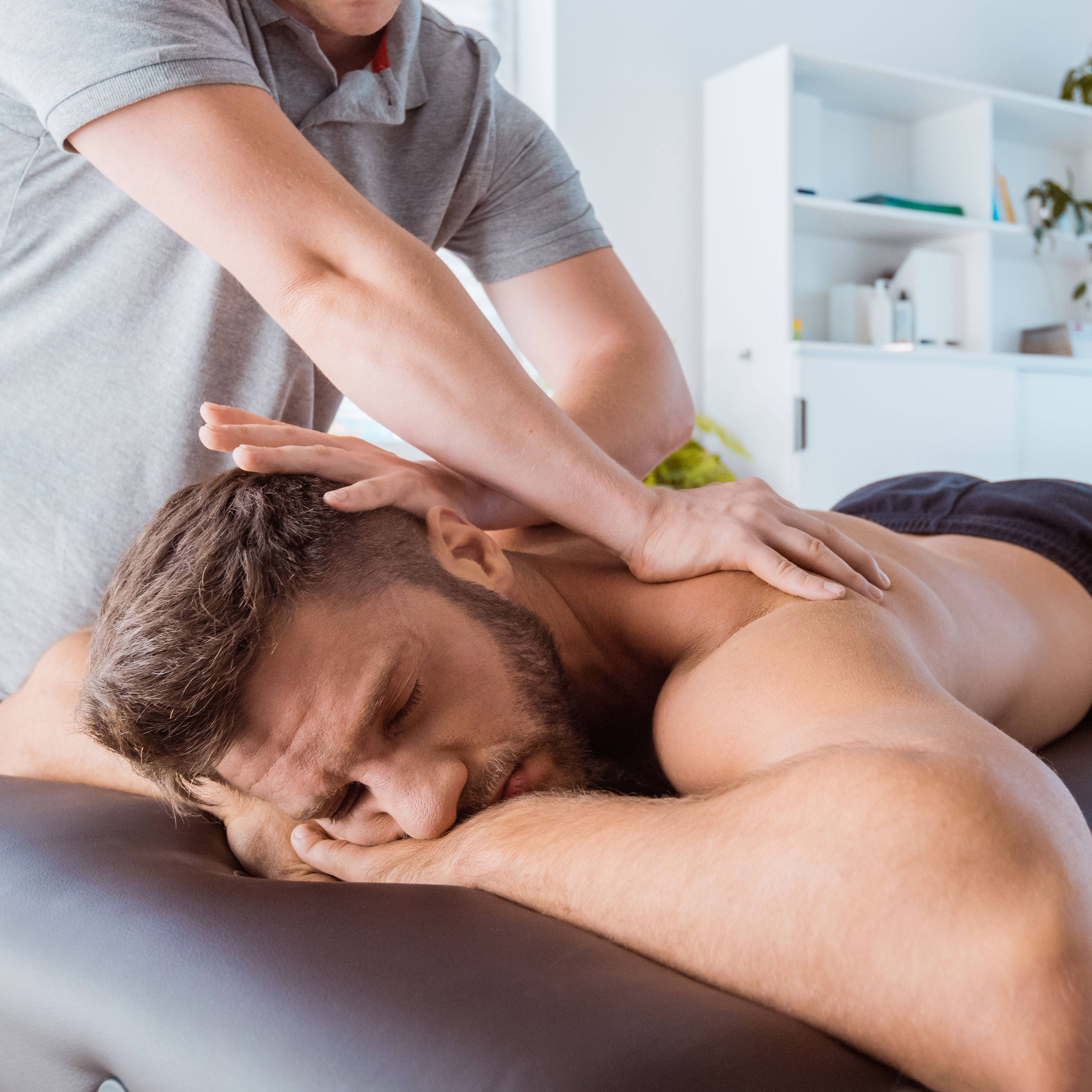 Massage therapist massaging back of the young man