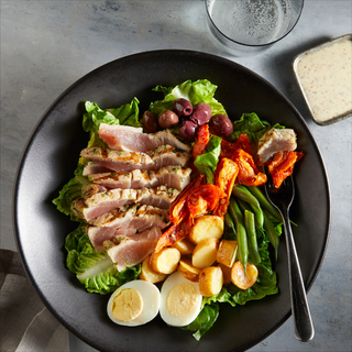 Ahi tuna niçoise salad with greens, sliced rare tuna, hard boiled eggs, steamed potatoes, olives in a black bowl with a fork on a grey background.