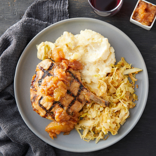 Light grey round dinner plate with creamy mashed potatoes, savory cabbage slaw and an apple glazed pork chop with a blue napkin on the side.