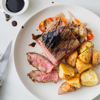 White dinner plate with balsamic-glazed flat iron steak with two slices cut off served with crispy potato wedges and extra balsamic glaze in a bowl on the side.