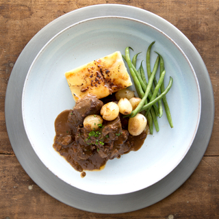 Beef bourguignon on a light blue plate with green beans and mashed potatoes and white pearl onions.